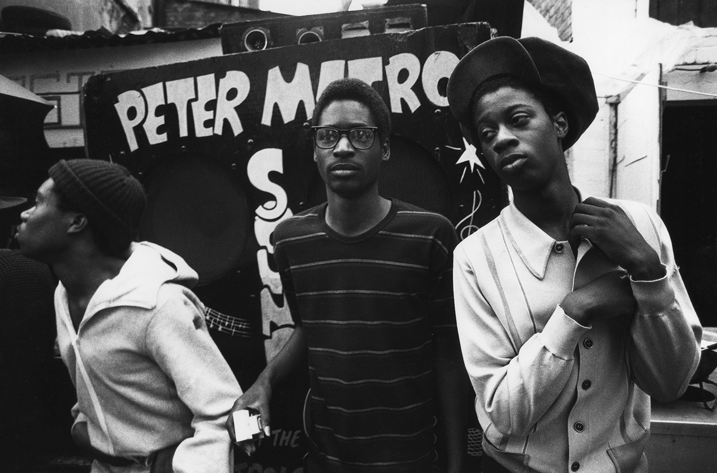 Three teenage boys next to the Peter Metro Sound System at Notting Hill Carnival, London, 1980s by Peter Anderson