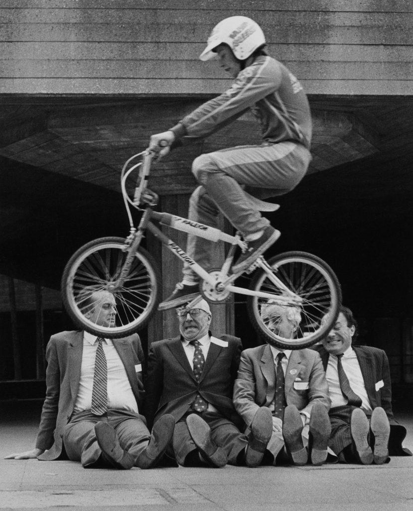 BMX rider jumps over local politicians at famous skateboarding spot The Undercroft skate park under the Southbank Centre, London, 1980s