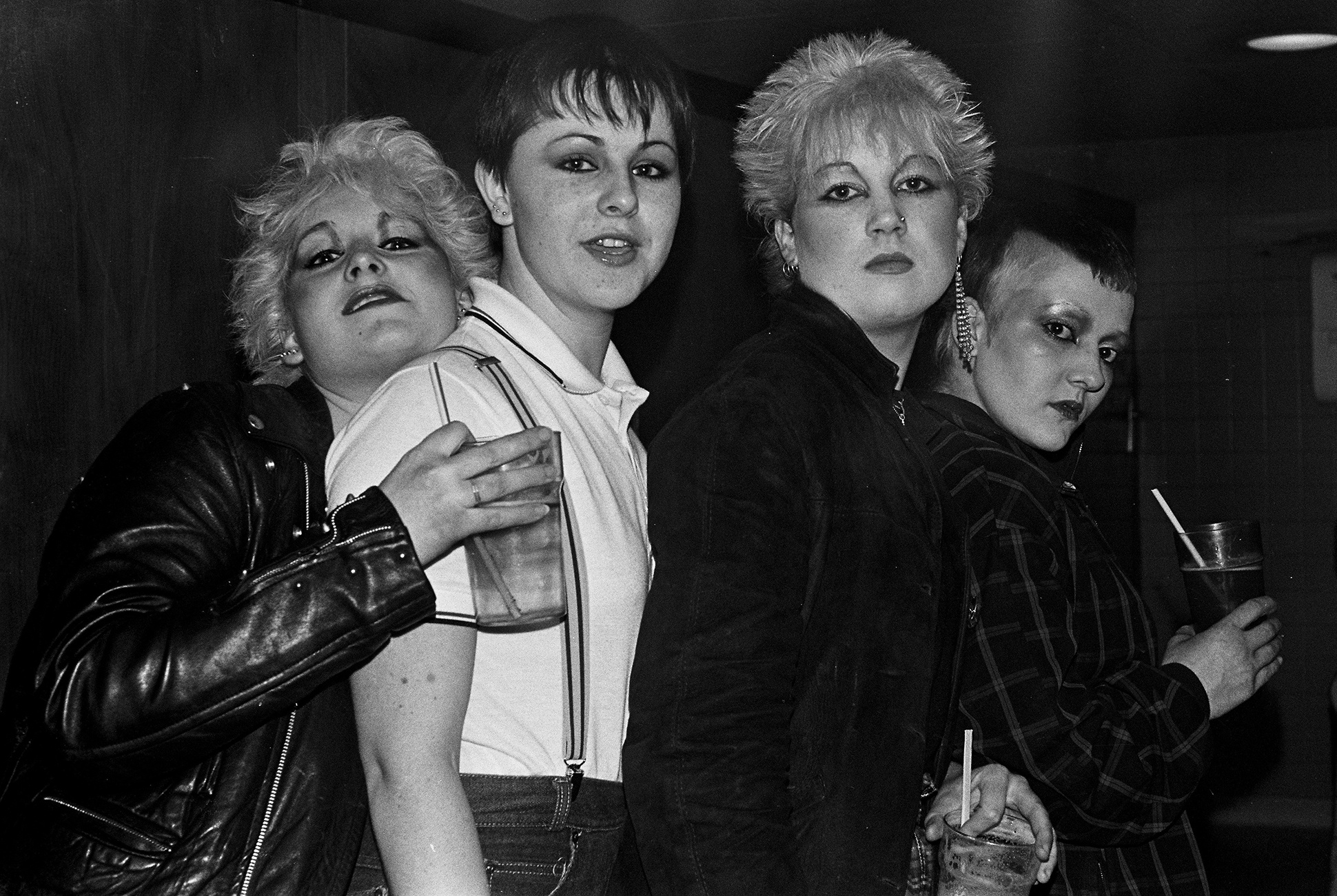 Punk and skinhead girls at a gig with peroxide hair, leather jackets and Fred Perry shirt, Hastings, 1981 by Clare Muller