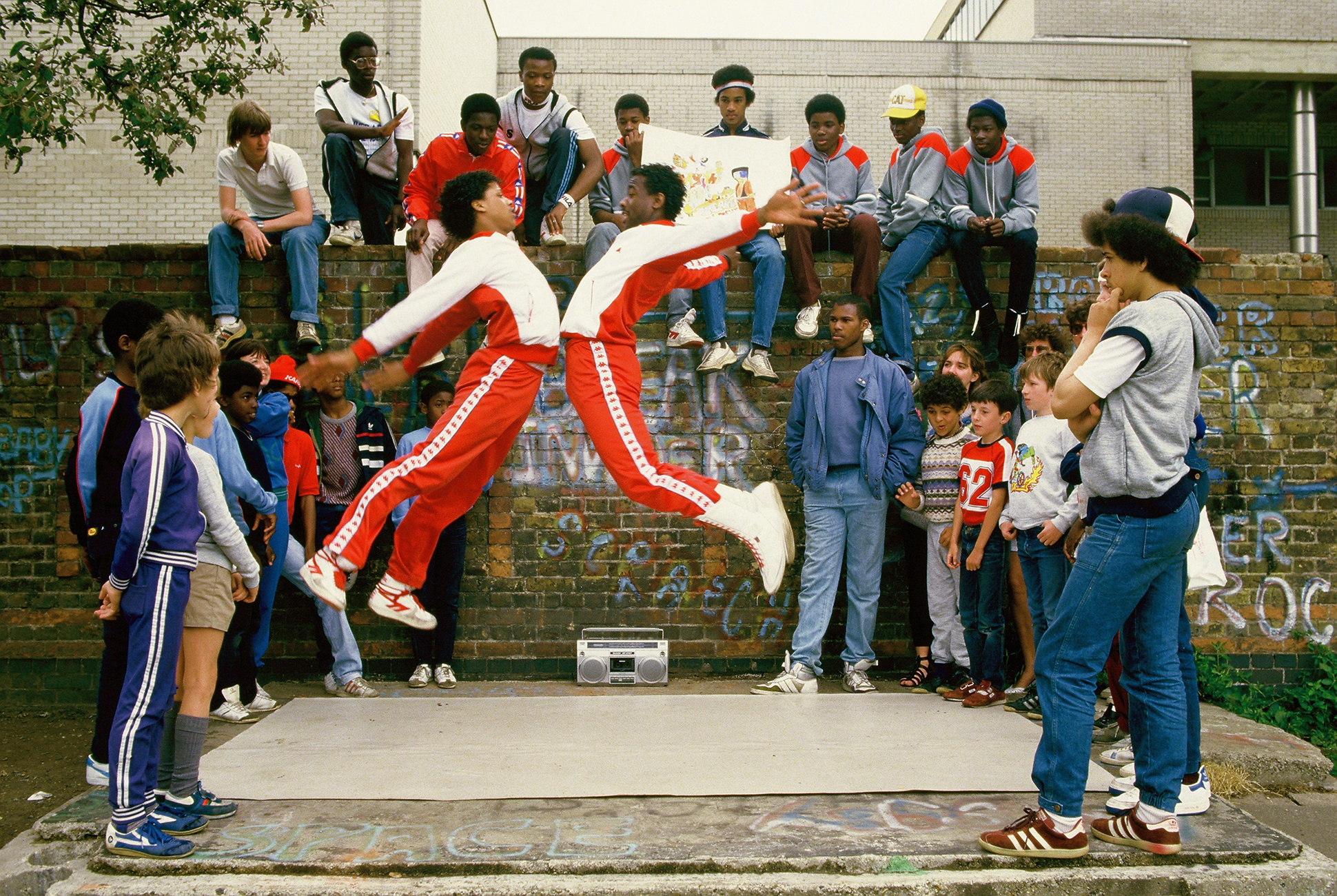 Two breakdancers in red Kappa tracksuits jump up during a breakdancing performance, London, 1983 by Clare Muller