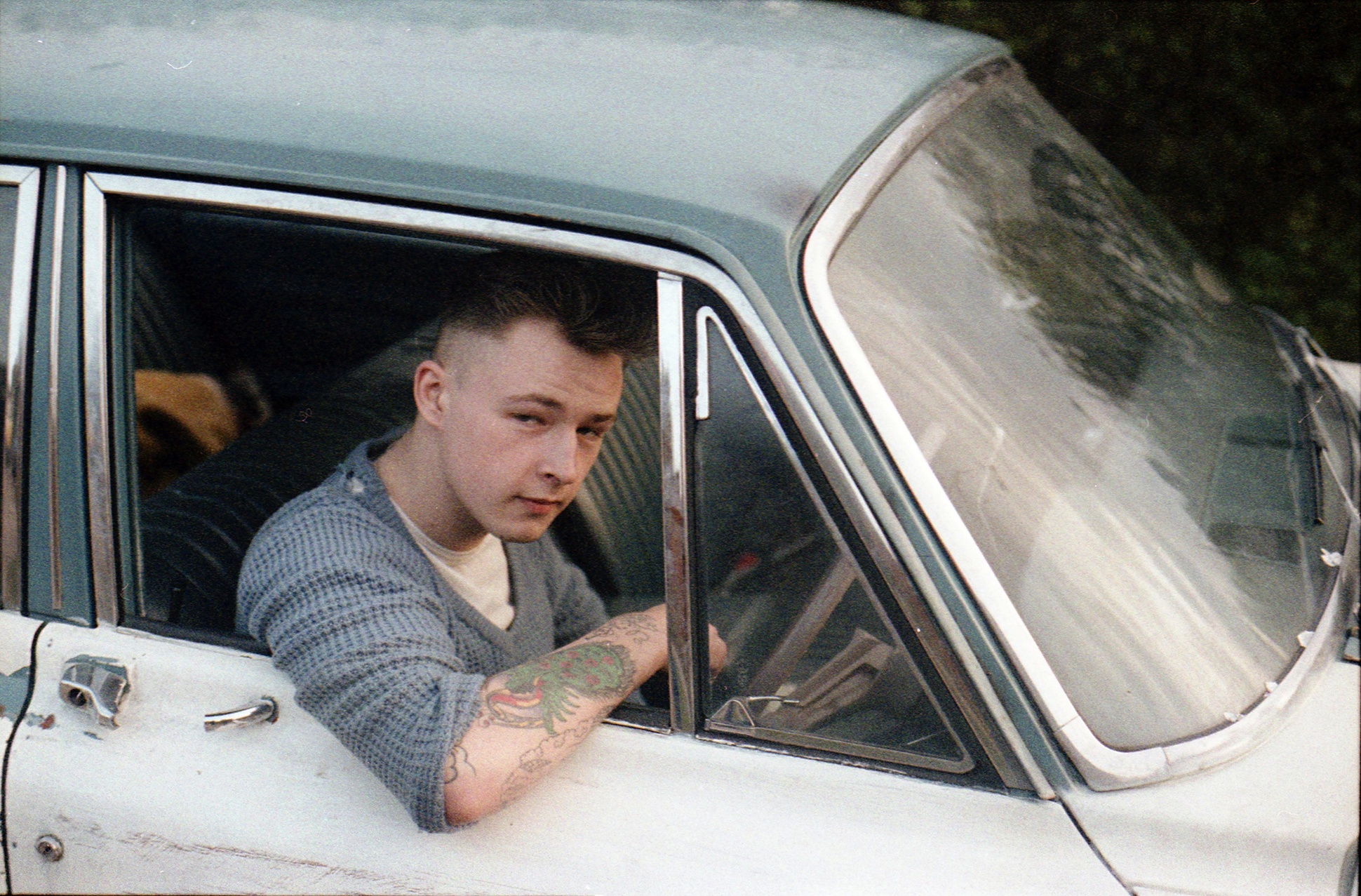 Rockabilly with traditional style tattoos on his arm in his car, High Wycombe, 1980s by Gavin Watson