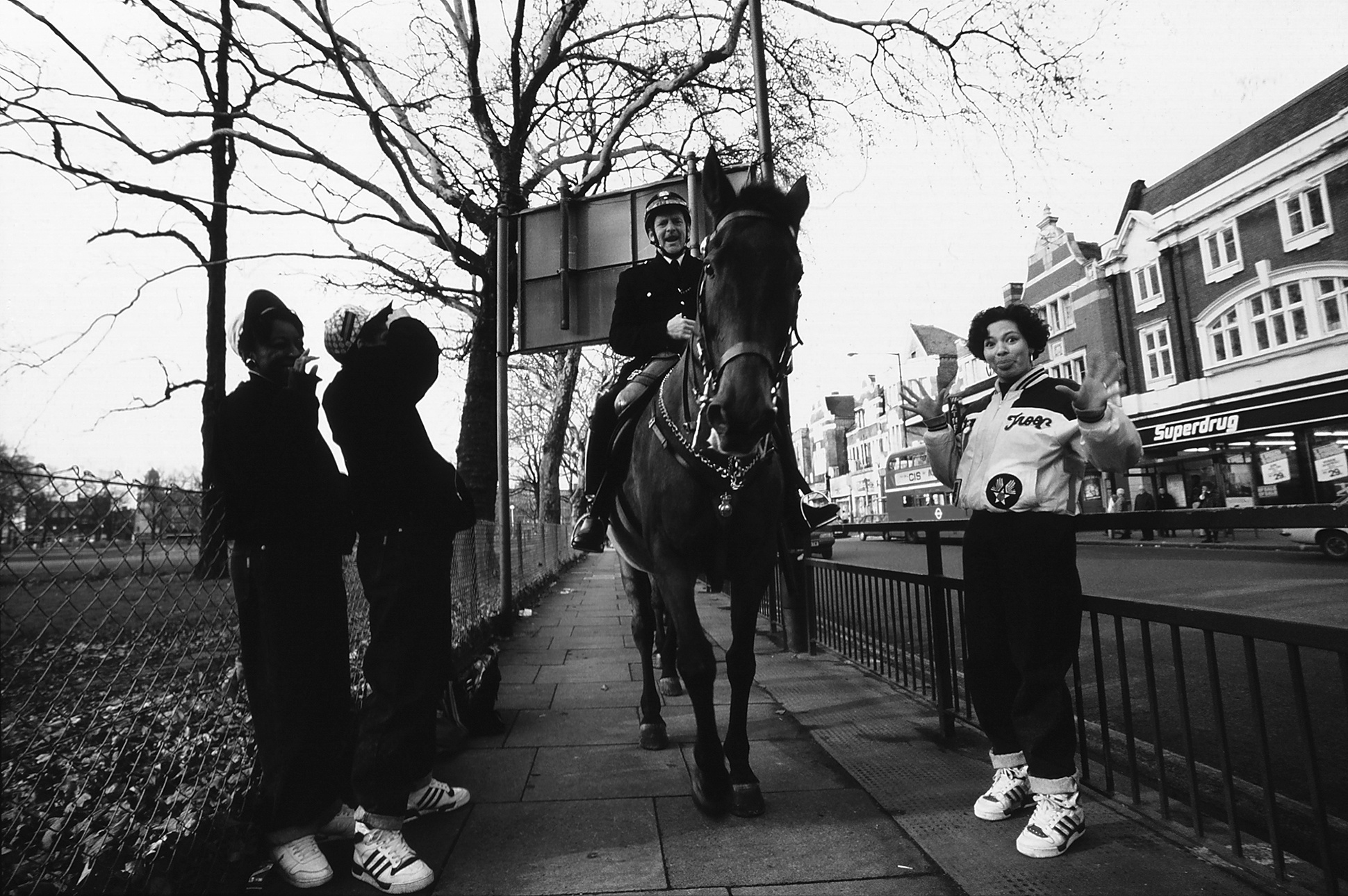 UK hip hop trio She Rockers, all in tracksuits, jump away from a mounted police officer, London, 1980s by Normski