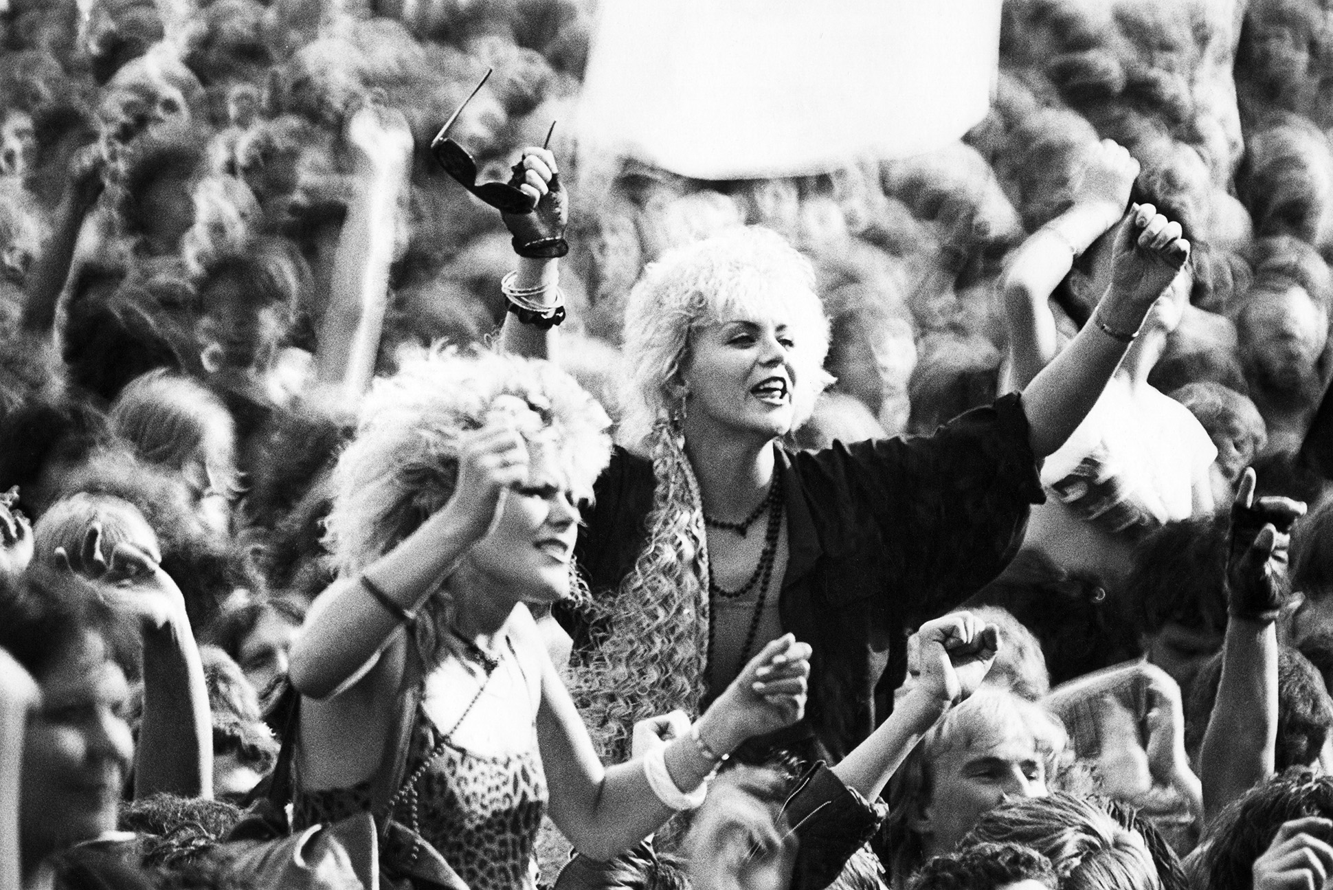 Two women on shoulders in the crowd at Reading Festival, 1980s by Peter Anderson