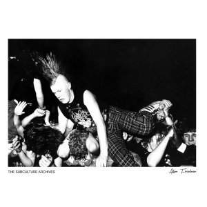 A punk with a mohawk, Slayer band t-shirt and tartan trousers crowdsurfing, Kilburn, 1990s by Adam Friedman