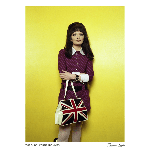 Mod girl in a dress with a beehive and Union Jack handbag, London, 1990s by Rebecca Lewis
