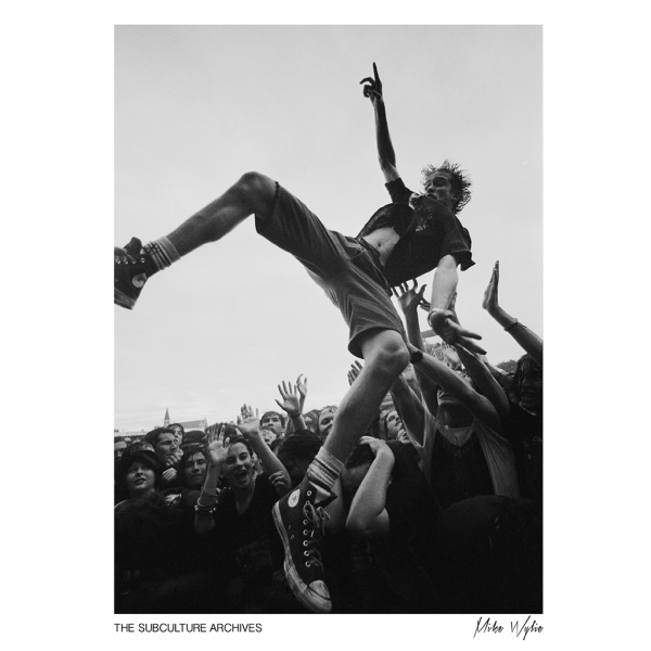 Grunge rock teenager crowdsurfing wearing Converse at a festival, 1990s by Mike Wylie